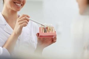 Dentista mostrando un implante en Clínica Aviñó, especialistas en implantes dentales