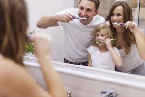 Niña pequeña cepillándose los dientes con sus padres tras las recomendaciones de Clínica dental Valencia