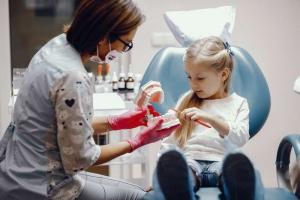 Dentista explicando a una niña cómo cepillarse los dientes correctamente